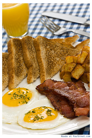 Breakfast meal on a white plate with two eggs,potato,toasted bread,bacon and orange juice.<br /> <br /> Orientation : vertical<br /> Concept : mealtime,food,morning