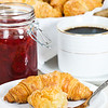 croissant breakfast in a plate. Strawberry jam and black coffee in the background. Shallow depth of field.