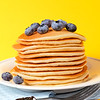 Hot pancake staked with blueberry fruit on a yellow background.