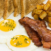 Breakfast meal on a white plate with two eggs,potato,toasted bread and bacon.<br /> <br /> Orientation : vertical<br /> Concept : mealtime,food,morning