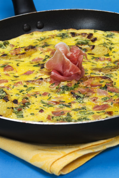 Frittata with potato, basil leaf, prosciutto meat and egg in a cookware pan. Shallow depth of field.