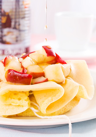 Pancake  with maple syrup falling on the apple fruit. Very shallow depth of field.
