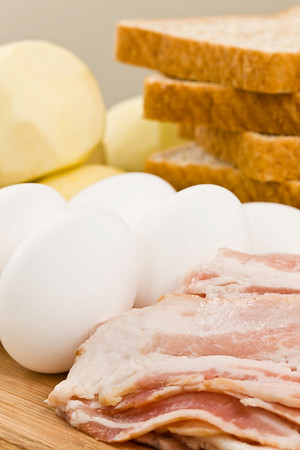 Raw ingredient ready to cook a gourmet meal breakfast. Food on a wooden cutting board. Potato,egg,bacon and whole wheat bread.<br /> <br /> Orientation : vertical<br /> Concept : cooking, mealtime,morning,