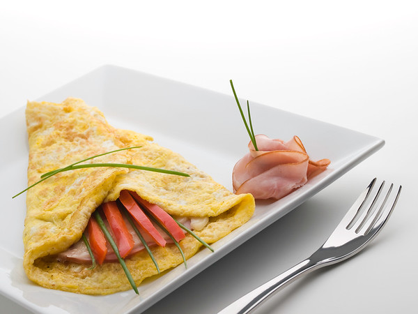 omelet on a white plate with ham,cheese and sweet pepper