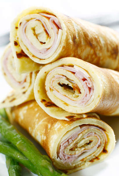 rolled ham and cheese crepe with asparagus on a white background.