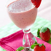 Strawberry smoothie with fresh fruit around the glass. Very shallow depth of field.