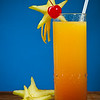 tropical drink with carambola, cherry and orange on a blue background. Shallow depth of field.