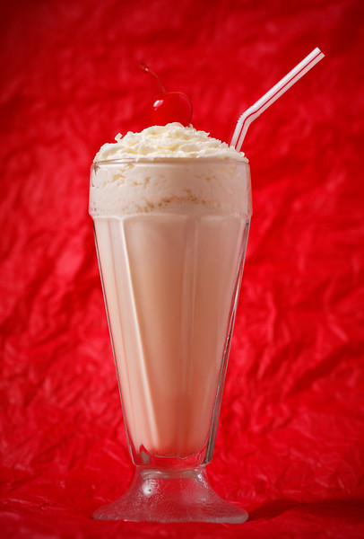 vanilla milkshake with whipped cream and cherry on the top. Focus on the cherry. Red background.