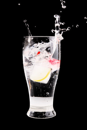 glass of water with fruit inside the ice cube splashing