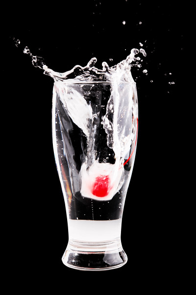 glass of water with a cherry inside the ice cube splashing