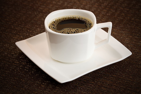 Dark coffee cup with brew on the top. White vessel with saucer dishware. Shallow depth of field and added vignetting.