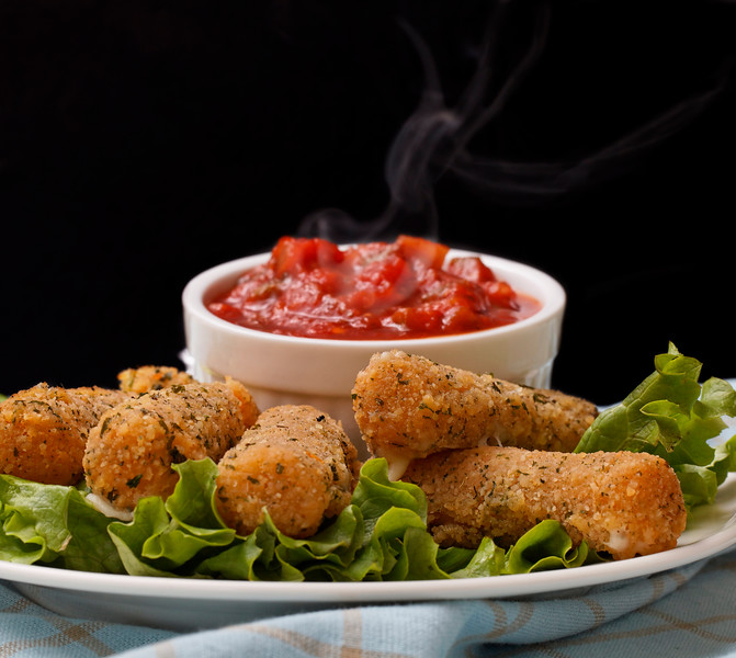cheese sticks appetizer on salad with very hot salsa sauce. Smoke on the salsa with a black background.