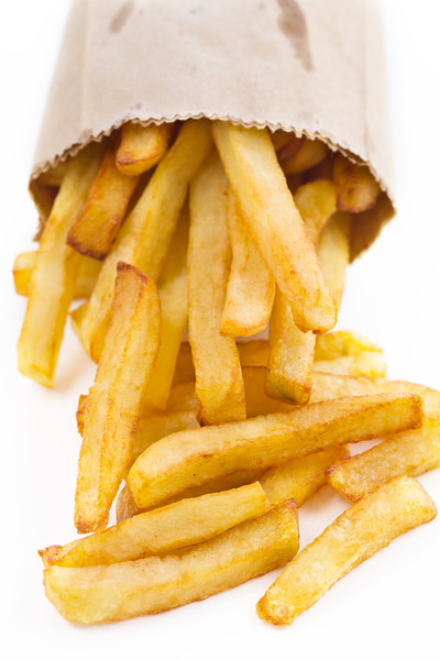 French fries in a small brown paper bag. Shallow depth of field.
