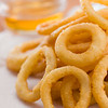 Stacked onion ring on a white waxed paper. Honey sauce  in the backgroundVery shallow depth of field.