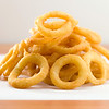 Stacked onion ring on a white waxed paper. Very shallow depth of field.
