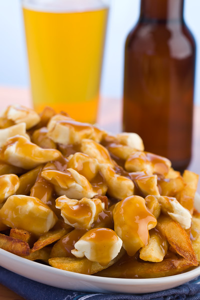 Poutine meal made with french fries, cheese curds and gravy. Beer in the background. Shallow depth of field.