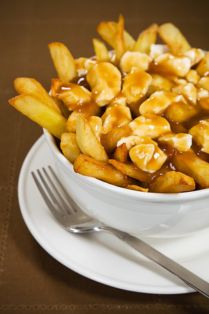 Poutine meal made with french fries, cheese curds and gravy. Very Shallow depth of field.