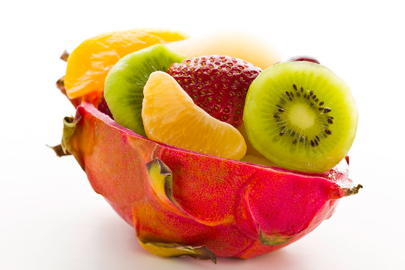 Bio fruit salad desert in a cuted pitahaya on a white background.