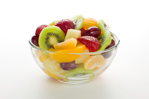 Fruit salad desert in a transparent bowl on a white background.<br /> <br /> Orientation : horizontal<br /> Concept and idea : health,healthy food, breakfast,freshness and bio.