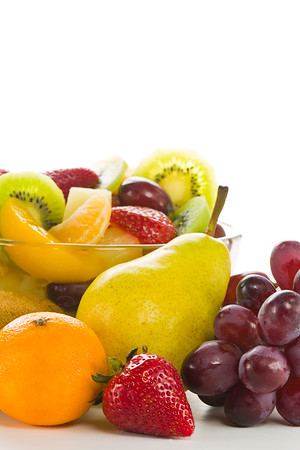 Fruit-salad desert in a transparent bowl on a white background with mixed fruit around. Lot of space to ad your text.<br /> <br /> Orientation : vertical<br /> Concept and idea : health,healthy food, breakfast,freshness and bio.