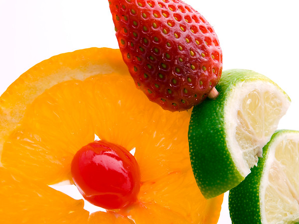 color photography with orange cherry strawberry and lemon on white background