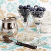 blueberry fruit in glass with sugar and cream in the background. Shallow depth of field.