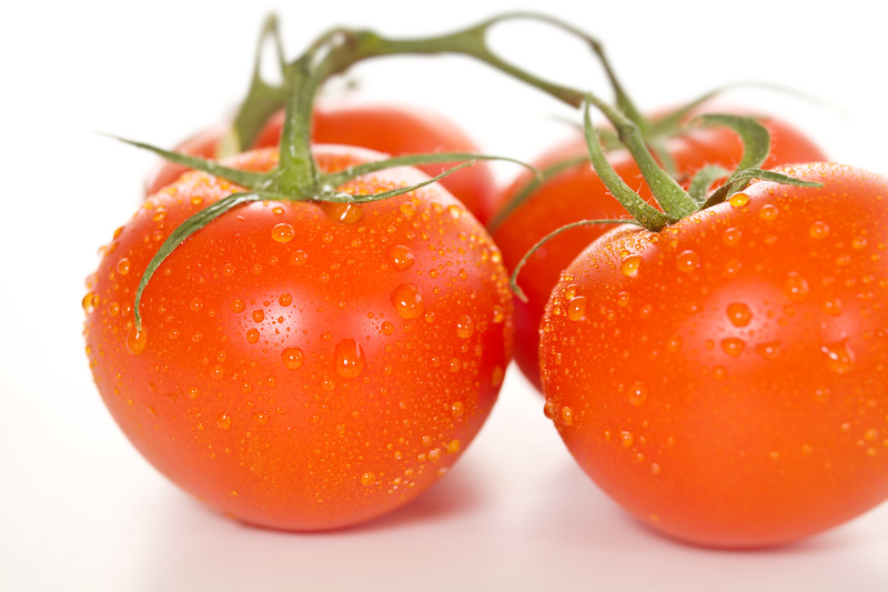 Fresh tomato on white background with water drop on it. Selective focus with very shallow depth of field.