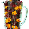 Frozen fruit in a glass pitcher blender  for a healthy smoothie. Backlit with white background.