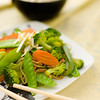 Vegetable stri fry  on a plate with a bowl of white rice in the background. Very shallow depth of field.