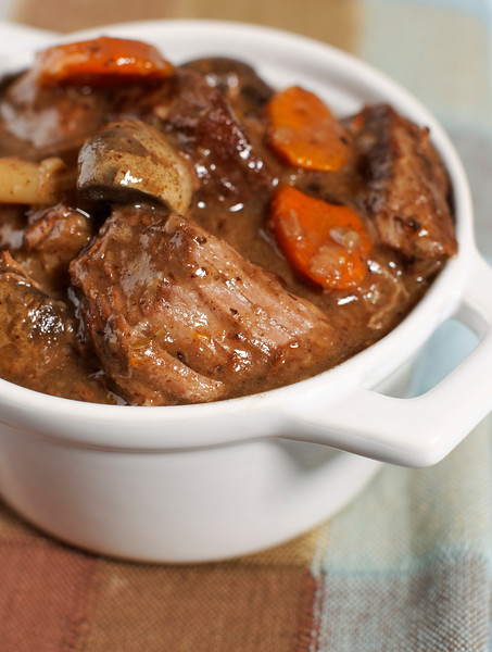 Delicious bourguignon beef stew in a small white bowl. Very Shallow depth of field.