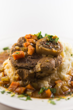 Osso buco meal with sauce,mashed potato and carrot vegetable. White background and very shallow depth of field.