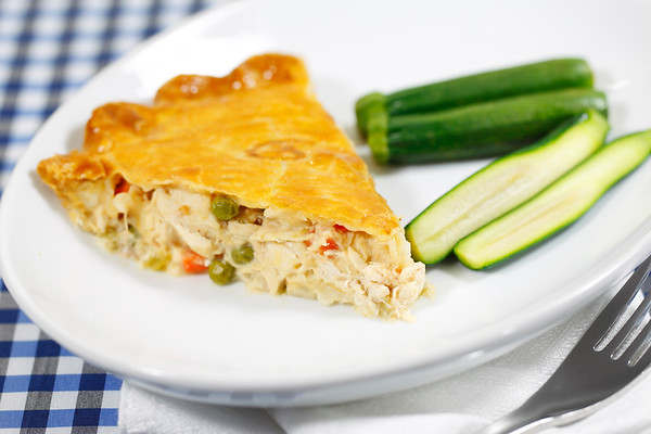 chicken pie meal in a white plate with vegetable on the side. Blue checkered tablecloth and shallow depth of field.