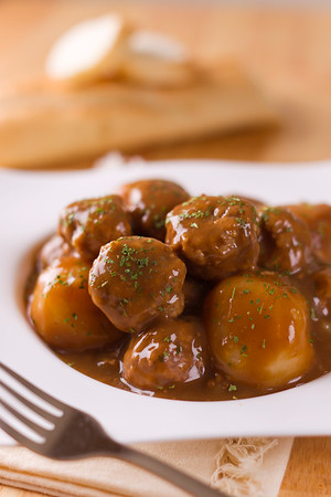 Meatball pork with potato in a brown sauce. Bread in the background.Shallow depth of field.