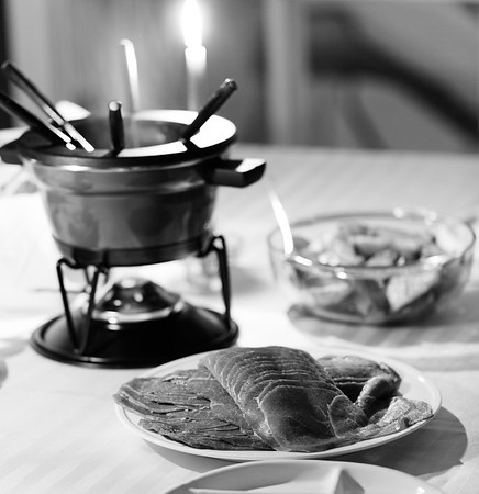 black and white photography with meat fondue dish  on a table. Very shallow depth of field.