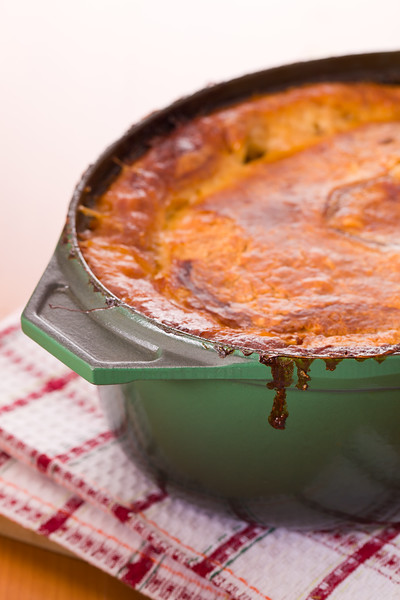 Cooked pot pie with beef, veal and pork meat inside a green oven cookware. Very shallow depth of field.