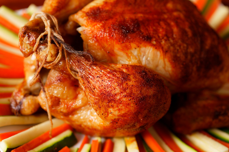 roasted chicken on a plate with vegetable. Very shallow depth of field.