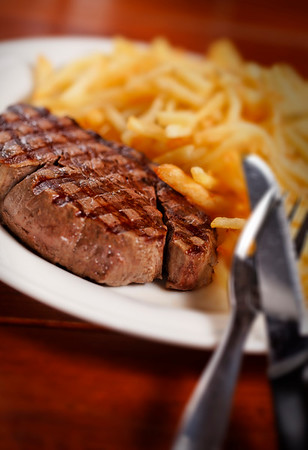 grilled steak and french fry on a white plate for a bistro style. Selective focus and shallow depth of field.