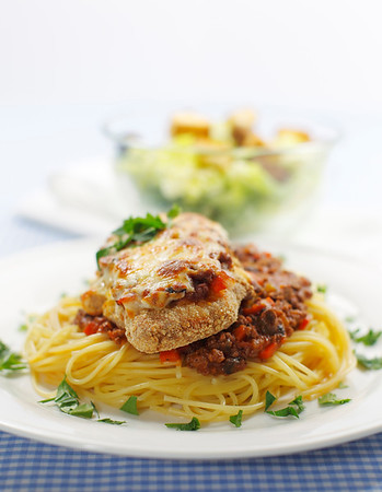 chicken parmigiana meal on a spaghetti with tomato and meat sauce. Caesar salad in the background.Shallow depth of field.