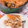 Pot pie with beef, veal and pork meat in a green oven cookware. Portion in a white plate.Very shallow depth of field.