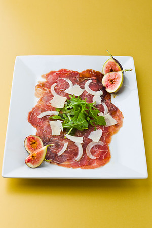 Red beef carpaccio in a white plate with salad, fig fruit, parmesan cheese and olive oil. Yellow background and shallow depth of field.