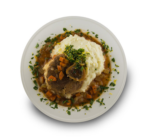 Osso buco meal in a plate with mashed potato, sauce and carrot vegetable. Isolated on white background with added shade  and very shallow depth of field.