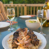 Outdoor meal with chicken and shrimp brochette on the rice. Alcohol white wine. Very shallow depth of field.