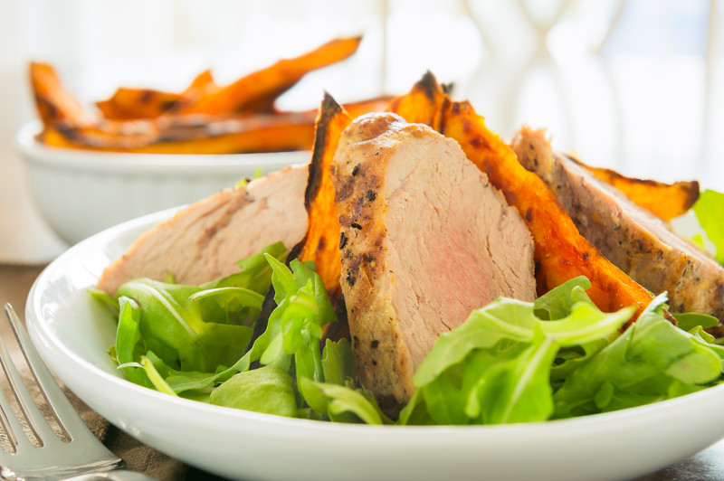 Healthy meal with sliced pork fillet with sweet potato and salad. Shallow depth of field.