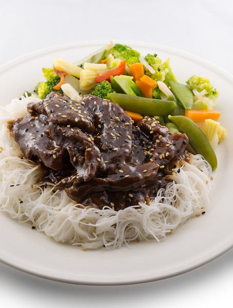 Teriyaki beef meat with rice vermicelli and vegetable in a white plate.