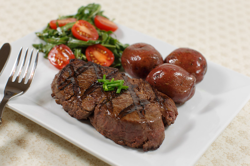 cooked filet mignon steak in a white plate with salad and little potatoes. Shallow depth of field.