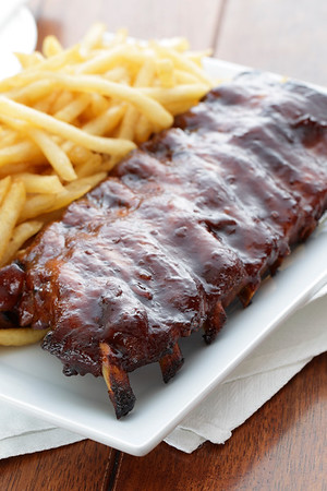 baked ribs with french fries on the side. Meat meal.