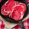 Two beautiful pieces of raw beef meat in a black iron frying pan. Shallow depth of field and red background.
