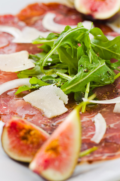 Red beef carpaccio in a white plate with salad, fig fruit, parmesan cheese and olive oil. Macro photography with shallow depth of field.