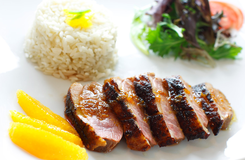 orange duck meal with rice and salad on the side. White plate.