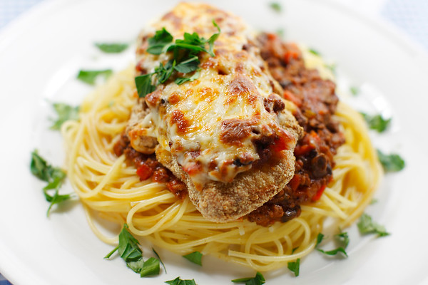 chicken parmigiana meal on a spaghetti with tomato and meat sauce. Shallow depth of field.
